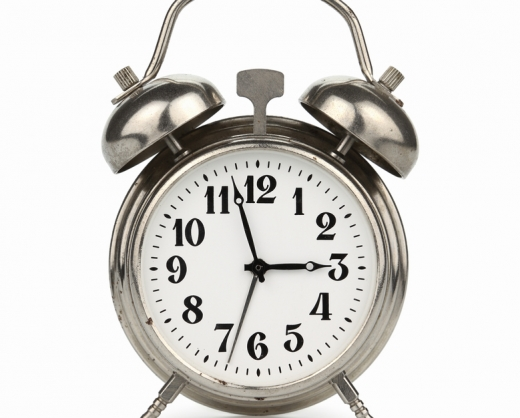 Silver plated old alarm clock, isolated on white background