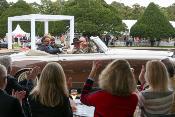 People wave from a vintage car at Hampton Court