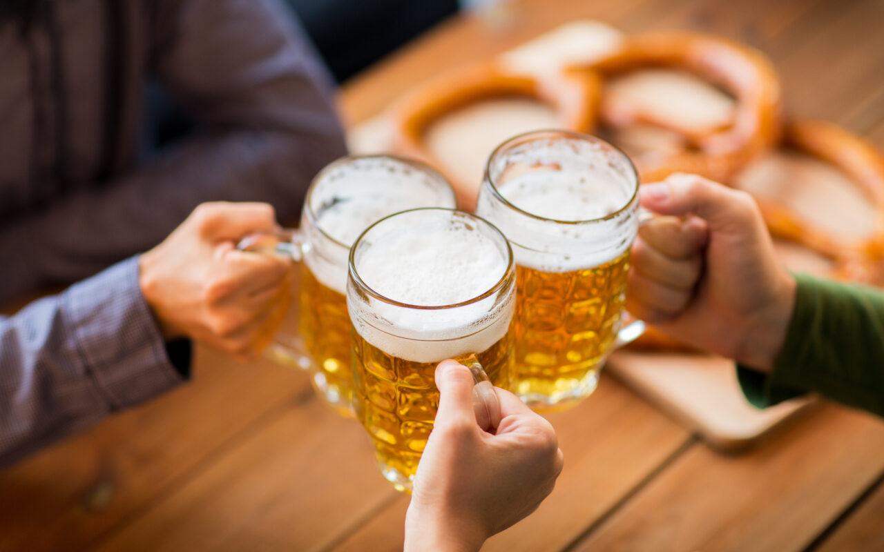close up of hands clinking beer mugs at bar or pub